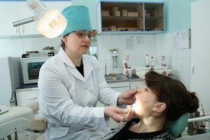 врач смотрит рот пациента